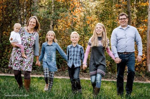 Mama, Papa und vier Kinder spazieren über die Wiese.